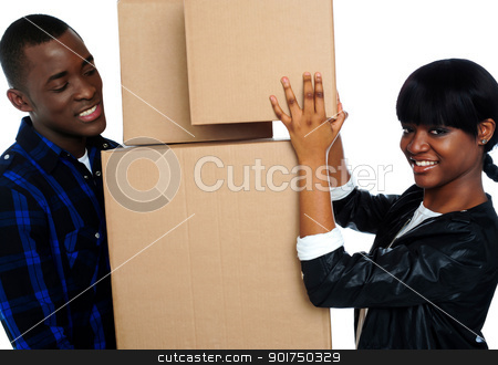 Young couple holding and moving boxes stock photo, Pretty woman placing boxes on large stack. Man holding all. by Ishay Botbol