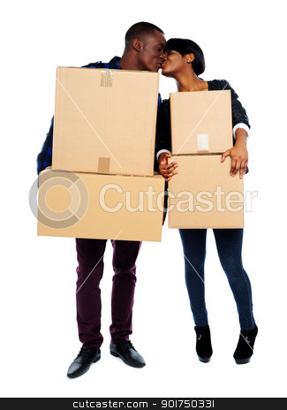 Couple holding cardboard boxes and kissing stock photo, African couple holding cardboard boxes and kissing. Full length portrait by Ishay Botbol   