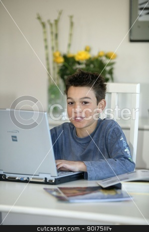 Preteen typing up his homework stock photo, Preteen typing up his homework by photography33