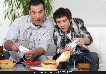 Father and son playing computer games and eating junk food stock photo
