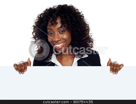 Young woman holding blank white placard stock photo, Portrait of happy young woman holding blank billboard against white background by Ishay Botbol