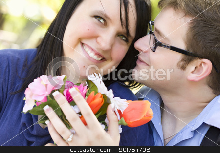 Attractive Young Man Gives Flowers to His Love stock photo, Attractive Young Man Gives Flowers to His Fiance Wearing the Engagement Ring. by Andy Dean