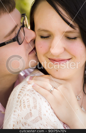 Young Engaged Couple Sharing a Moment in the Park stock photo, Attractive Young Engaged Couple Sharing an Intimate Moment in the Park. by Andy Dean