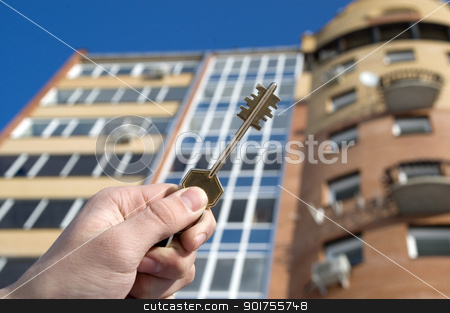 Modern Condominium stock photo, On a background of a modern brick house, hand with keys from an apartment.  by Yury Ponomarev