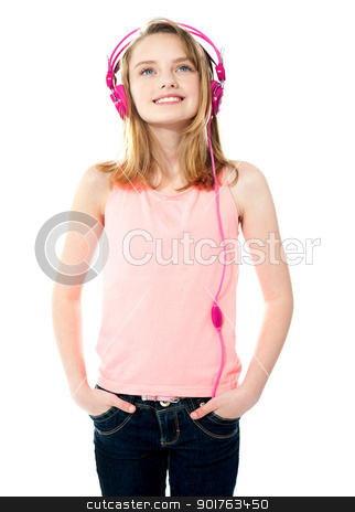 Adorable girl tuned into music stock photo, Attractive teenager listening to music on her music player by Ishay Botbol   