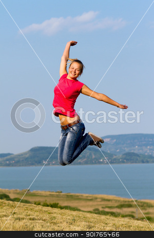 Jumping stock photo, Happy young girl jumping on the shore  by ARPAD RADOCZY