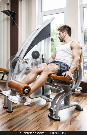 leg press stock photo, A handsome young muscular sports man doing leg press by Markus Gann