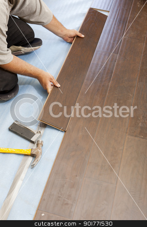 Man Installing New Laminate Wood Flooring stock photo, Man Installing New Laminate Wood Flooring Abstract. by Andy Dean