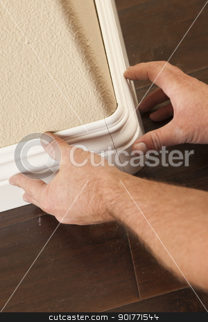 Contractor Installing New Baseboard with Bull Nose Corners and N stock photo, Contractor Installing New Baseboard with Bull Nose Corners and New Laminate Flooring Renovation Abstract. by Andy Dean