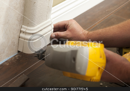 Nailing New Baseboard with Bull Nose Corners and New Laminate Fl stock photo, Contractor Nailing New Baseboard with Bull Nose Corners and New Laminate Flooring Renovation Abstract. by Andy Dean