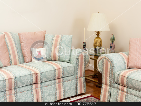 Modern living room with couches stock photo, Modern living room with green and pink settees, glass table by Steven Heap
