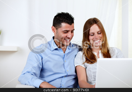 Lovely couple smiling and using a laptop stock photo, Portrait of a lovely couple smiling and having fun on laptop at home indoor by pablocalvog