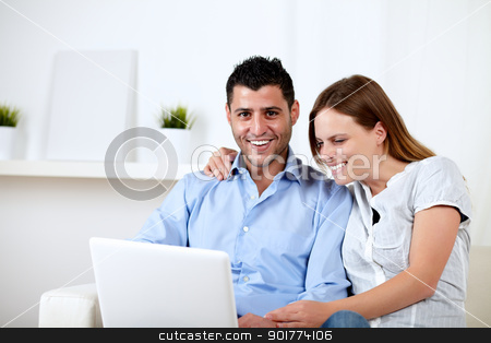 Couple having fun on laptop at home stock photo, Portrait of a friendly couple having fun on laptop at home indoor by pablocalvog