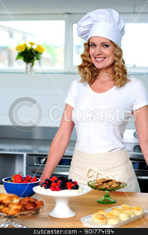 An isolated shot of a beautiful  woman chef stock photo, An isolated shot of a beautiful  woman chef standing in kitchen by Ishay Botbol