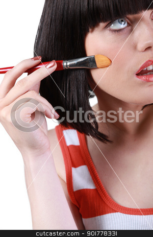 Pretty girl applying blush on her cheek stock photo, Pretty girl applying blush on her cheek by photography33