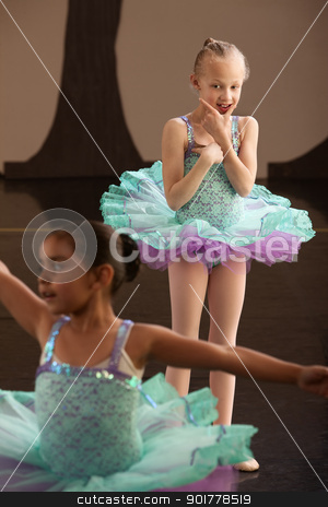 Young Ballet Student Watches Friend stock photo, Two little girls in ballet dresses practice in a studio by Scott Griessel