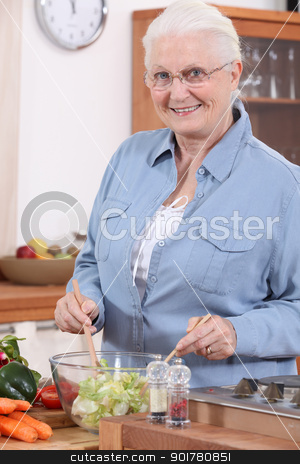 Senior woman preparing salad stock photo, Senior woman preparing salad by photography33