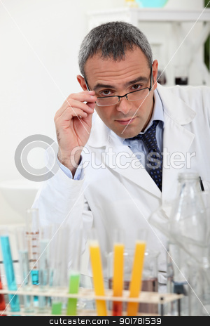 scientist touching his glasses behind test tubes in a laboratory stock photo, scientist touching his glasses behind test tubes in a laboratory by photography33