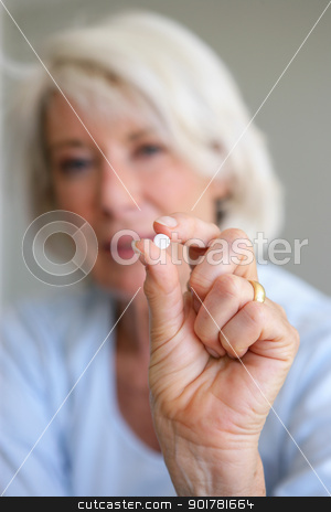 Older woman holding a pill stock photo, Older woman holding a pill by photography33