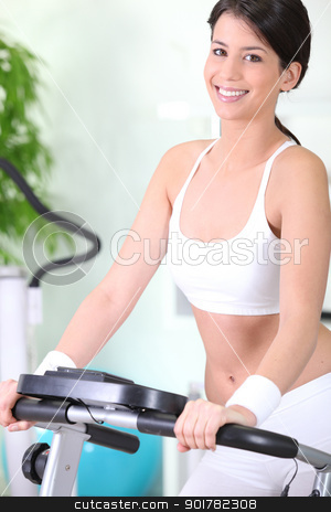 Woman cycling in the gym stock photo, Woman cycling in the gym by photography33