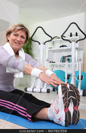 Woman touching her toes on an exercise mat stock photo, Woman touching her toes on an exercise mat by photography33