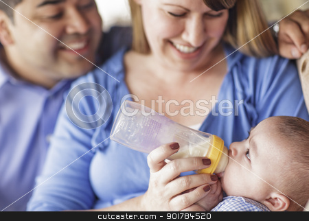 Happy Mixed Race Couple Bottle Feeding Their Son stock photo, Happy Attractive Mixed Race Couple Bottle Feeding Their Son. by Andy Dean