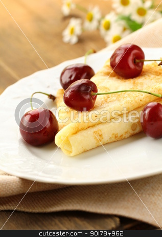 Sweet crepe pancake with  cherries on a wooden table stock photo, Sweet crepe pancake with  cherries on a wooden table by Olga Kriger