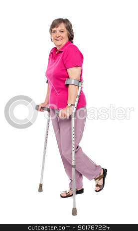 Smiling senior woman walking with crutches stock photo, Smiling senior woman walking with crutches. All on white background by Ishay Botbol