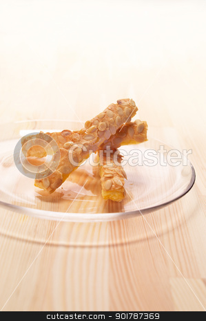 sunflower seeds puff pastry sticks stock photo, sunflower seeds puff pastry sticks on a glass transparent plate over pine wood table by Francesco Perre