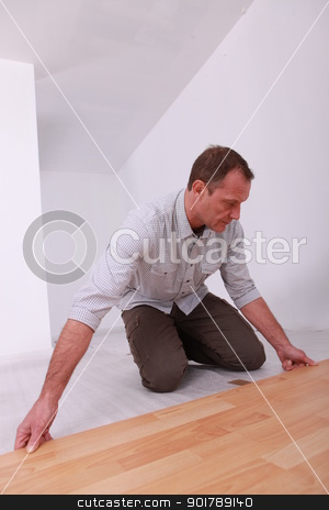 Man installing wooden flooring stock photo, Man installing wooden flooring by photography33