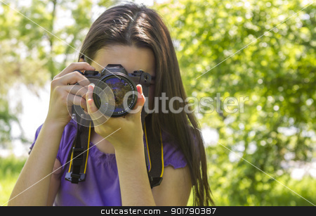Young girl taking photos at summer green park stock photo, Portrait of brunette girl, making photos at summer green park. by manaemedia