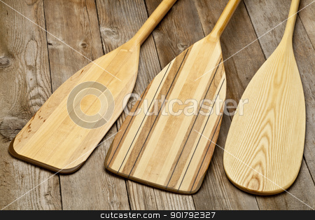 wooden canoe paddles stock photo, blades of three wooden canoe paddles of different shape against grunge wood surface by Marek Uliasz