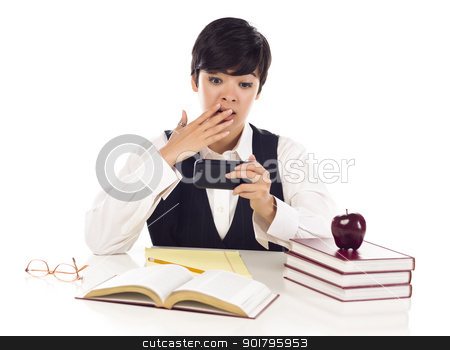 Pretty Mixed Race Female Student Shocked at Cell Phone Message stock photo, Pretty Mixed Race Female Student at Desk with Books Has Shocked Look from Cell Phone Message Isolated on a White Background. by Andy Dean