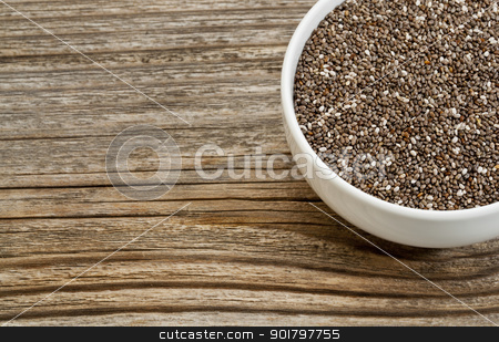 chia seeds stock photo, chia seeds - white ceramic bowl on a grained wood, copy space by Marek Uliasz