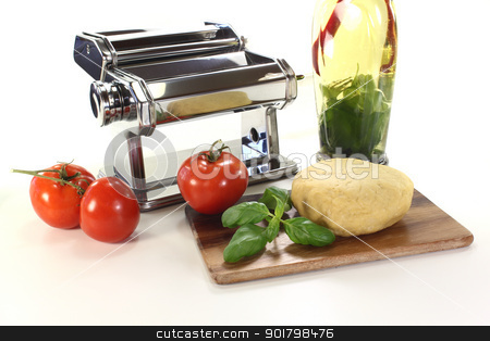 Noodle dough with basil and oil stock photo, Noodle dough in a pasta machine with tomatoes, herbs oil and basil by Marén Wischnewski