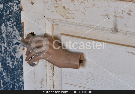 mannequin doll hand old door stock photo, Detached mannequin doll hand pulling old door handle in haunted house. by sirylok