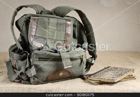Backpack stock photo, Tarpaulin backpack and old books on the canvas by Sergej Razvodovskij