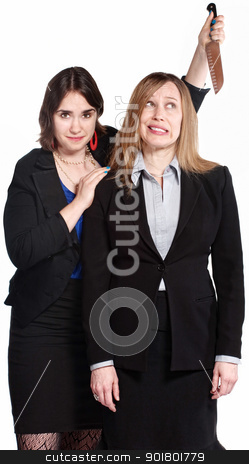 Woman Threatening Coworker stock photo, Mean female co-workers with knife behind her head by Scott Griessel