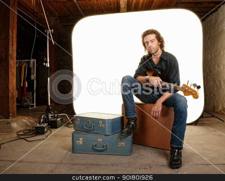 Musician With Guitar in Studio stock photo, Young musician with guitar in photography studio by Scott Griessel