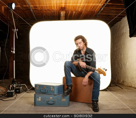 Guitar Player in Studio stock photo, Attractive man with guitar in photography studio by Scott Griessel