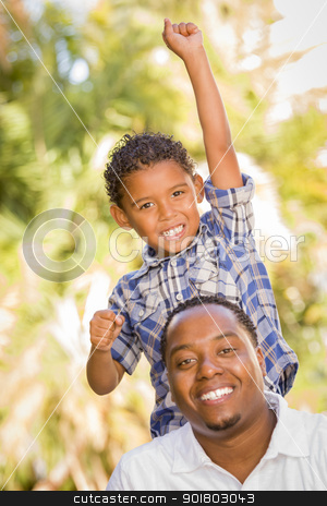 Mixed Race Father and Son Cheering with Fist in Air stock photo, Happy Mixed Race Father and Son Cheering with Fist in the Air at the Park. by Andy Dean