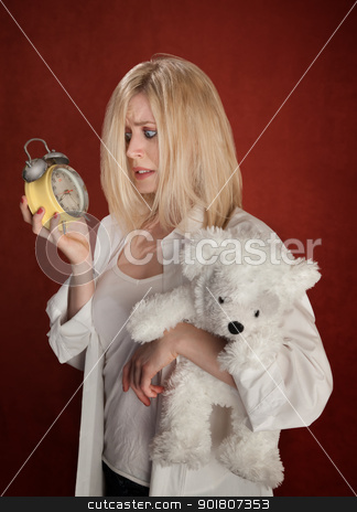 Sleepy Head stock photo, Pretty blond woman with bear and clock wakes up late by Scott Griessel