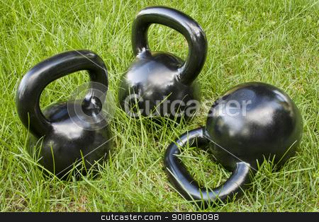 heavy kettlebells in grass stock photo, three heavy iron  kettlebells in green grass - outdoor fitness concept by Marek Uliasz