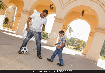 Mixed Race Father and Son Playing Soccer in the Courtyard stock photo, Mixed Race Father and Son Playing Soccer Outside in the Courtyard. by Andy Dean
