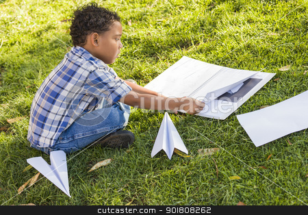 Mixed Race Boy Learning How to Fold Paper Airplanes stock photo, Mixed Race Boy Learning How to Fold Paper Airplanes Outdoors on the Grass. by Andy Dean