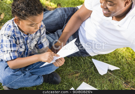 Mixed Race Father and Son Playing with Paper Airplanes stock photo, Happy Mixed Race Father and Son Playing with Paper Airplanes in the Park.  by Andy Dean