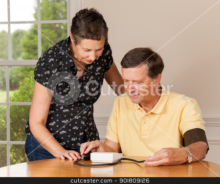 Senior man taking blood pressure with wife stock photo, Senior caucasian retired male taking blood pressure at home by Steven Heap