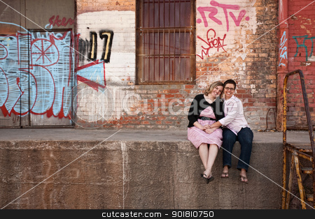 Friends Sitting at Dock stock photo, Two European women holding hands while sitting on a loading dock by Scott Griessel