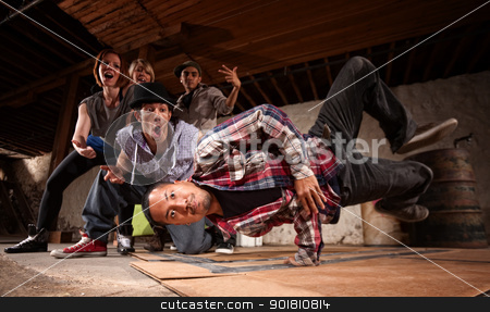 Young Man Spins on His Hand stock photo, Young Asian man performs break dancing moves on cardboard by Scott Griessel