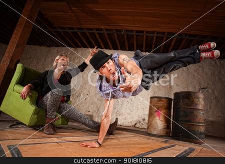 Break Dancer in Mid Air stock photo, Handsome Latino break dancer in mid air with cheering friend by Scott Griessel